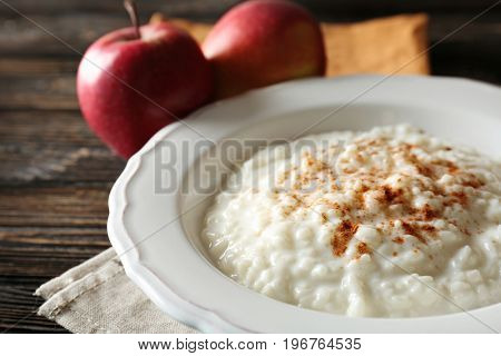 Delicious rice pudding with cinnamon on wooden background
