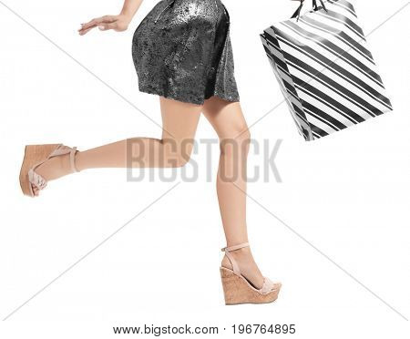 Young woman with beautiful legs carrying shopping bag on white background
