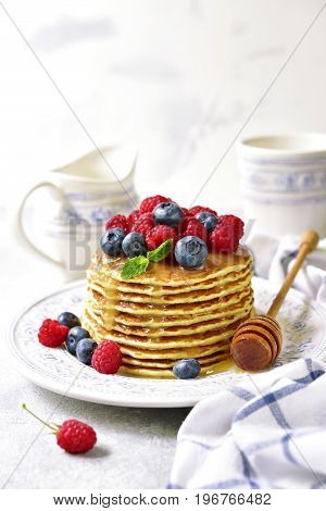 Homemade pancakes with honey and fresh berries on a light slatestone or concrete background.