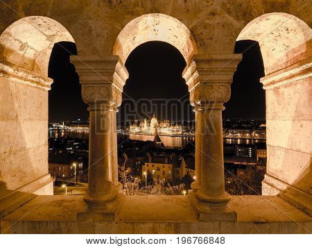 Night view of the famous Hungarian Parliament across the river Danube in Budapest, as seen through the arches of Buda Castle Fishermen's Bastion.