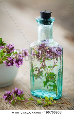 Vintage Bottle Of Thyme Infusion And Mortar Full Of Thymus Serpyllum Flowers. Herbal Medicine.