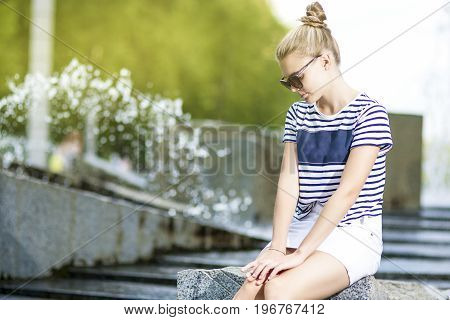 Portrait of Shy Caucasian Teenage Girl Posing in Green Summer Park. Sitting on Long Stone. Horizontal Image Orientation