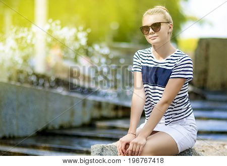 Teenager Concepts. Portrait of Shy Caucasian Teenage Girl Posing in Green Summer Park. Sitting on Long Stone. Horizontal Image Composition