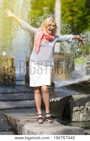 Portrait of Funny Mature Middle Aged Smiling Blond Woman Wearing Spectacles Posing Outdoors in Park. Showing Outstretched hands Against Nature Background. Vertical Image