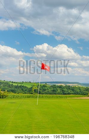 Golf field with green grass red flag and cloudy blue sky. Golf course