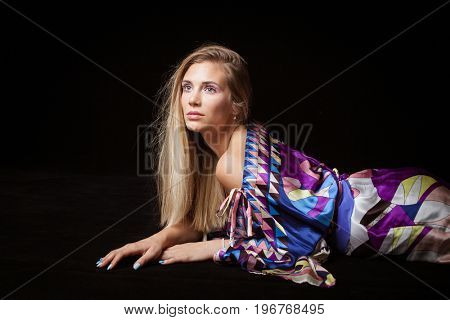 beauty young blonde woman portrait with interesting  makeup eyelashes and crystals in colorful silky dress studio
