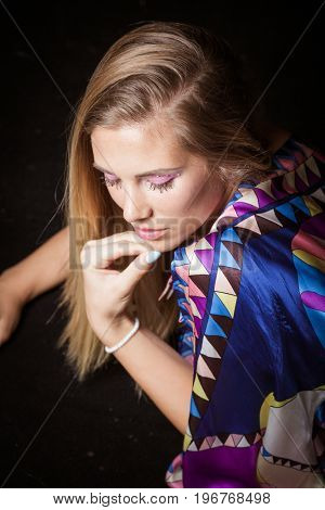 beauty young blonde woman portrait in colorful silky dress with interesting  makeup  crystals studio shot