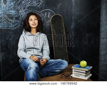 young cute teenage girl in classroom at blackboard seating on table smiling, modern hipster concept, lifestyle people close up