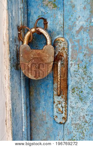 an old wood blue painted door with metal rusted latch, padlock and antique door handle.Vintage lock