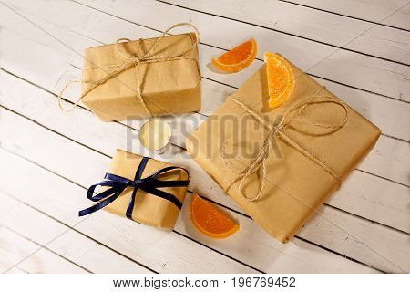 Gift festive box with decoration and blue ribbon on white wooden rustic background. Soft selective focus.
