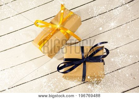 New year and Christmas gift boxes in rustic style on a wooden white background. Snow and the sparkle of xmas winter snowflakes. Eve decorations. Joyeux Noel