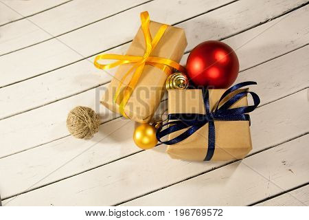 New year and Christmas gift boxes in rustic style on a wooden white background. Snow and the sparkle of xmas winter snowflakes. Eve decorations. Christmas balls.