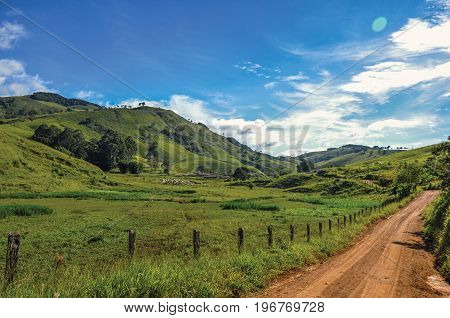 View of rural road next to forest and green hills near the town of Joanópolis. In the countryside of São Paulo State, a region rich in agricultural and livestock products, southwestern Brazil