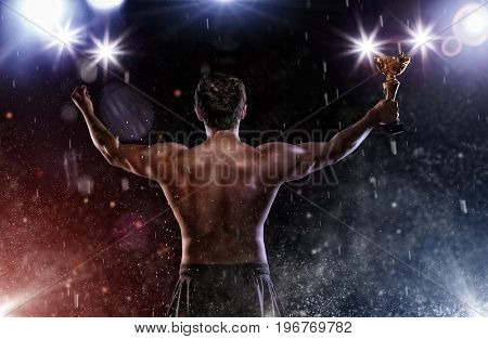 Back view of man fighter holding trophy cup in hands, victory gesture. Concept of hard sport, glory and success. Very high resolution image