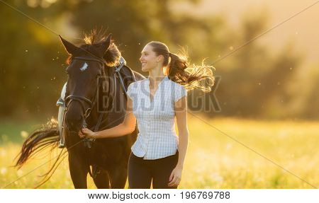 Young woman running with her horse in evening sunset light. Outdoor photography with fashion model girl.