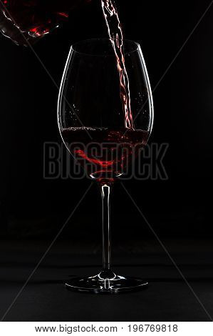 Red wine pouring in wineglass over black background.