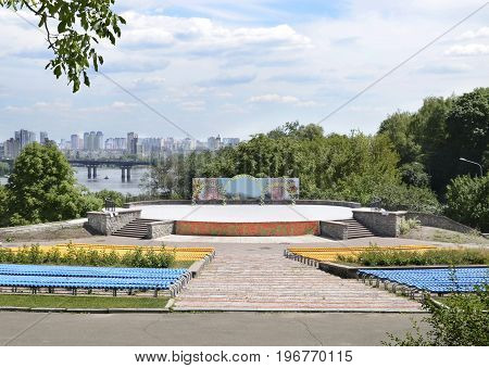 Summer area with seats and a stage against the background of the bridge the river and the city