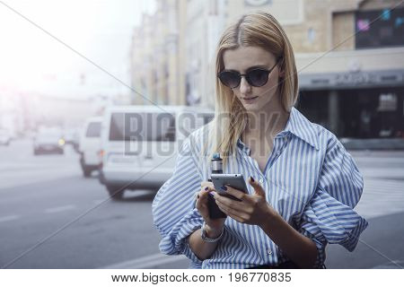 Blonde haired woman using cellphone and electronic cigarette on the background of street