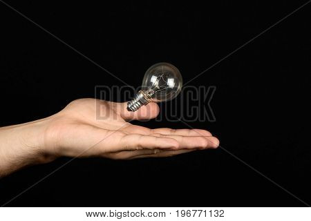 Male Hand Catches The Incandescent Bulb Close Isolated On Black Background. The Concept Of Electrici