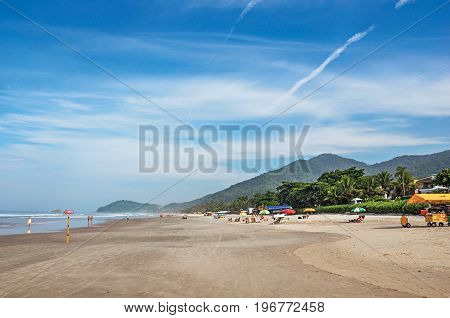 View of sand, sea, forest on the hill and people in a blue sunny day at the beach of Juquey, an amazing and tropical village in the coast of the São Paulo State, southwestern Brazil.