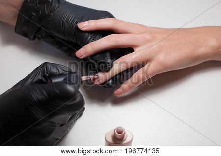 Manicurist black gloves doing a manicure at the beauty salon on a white background. Nail Polish colors Nude. Beautiful women's hands.