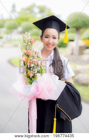 Women Is A Graduate Holding A Bouquet And Smiling For The Camera With Happy Successful Of Education