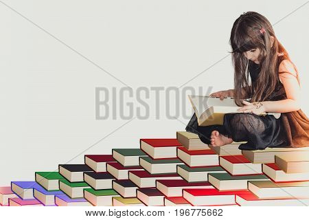 A little cute girl in a black dress sitting on pile of books and reading a book increasing knowledge being wisdom and intelligence.