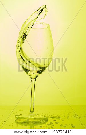 Water splashing out of a tall wine glass in color