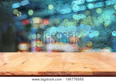 Empty top of wood table with raindrop on window in rainy night city background.