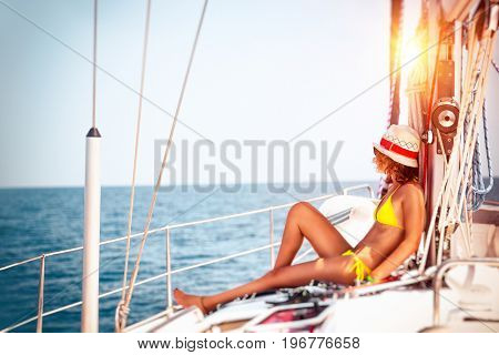 Woman relaxing on sailboat, slim model tanning on the deck of the yacht in bright sunny day, enjoying sailing adventures, luxury summer vacation