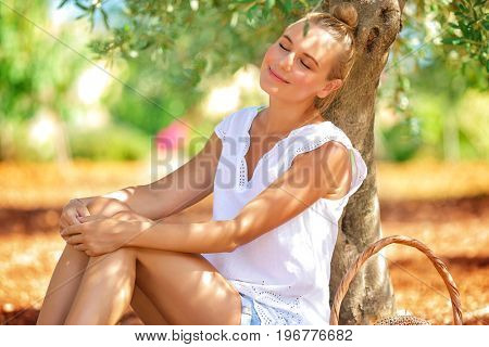 Farmer girl sleeping under an olive tree in the garden, resting in a countryside, enjoying warm sunny autumn day, harvest season