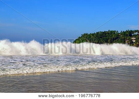 High storm waves on the ocean shore. Palm trees on a background