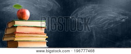 School accessories, books and fresh apple against chalkboard