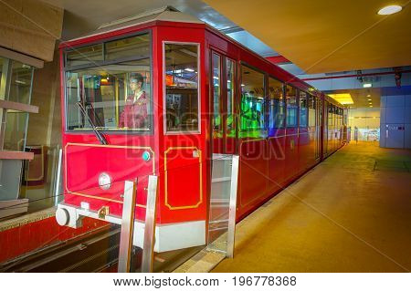 HONG KONG, CHINA - JANUARY 22, 2017: A Peak Tram car drives inside of the bus stop at Peak Tram, is a funicular railway in Hong Kong, which carries both tourists and residents to the upper levels of Hong Kong Island.