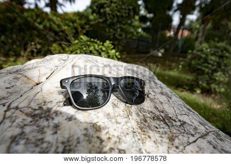 Black sunglasses on Terrazzo floor, marble table,rock