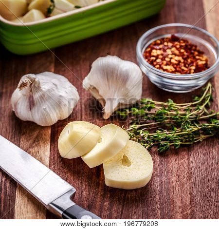 Preparing ingredients for roasted garlic includes fresh thyme and crushed red pepper. Chopped garlic in in a ceramic baking dish. Knife and roasting pan also shown