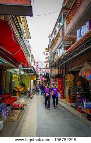 HONG KONG, CHINA - JANUARY 26, 2017: Unidentified people walking in the sidewalk in old fishermen village Tai O with rustic houses on loccated in Hong Kon, China.