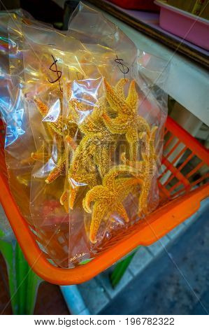 Dry sea stars inside of a plastic bags, in an orange baskets, in a market in fishermen town in lantau, Hong Kong, China.