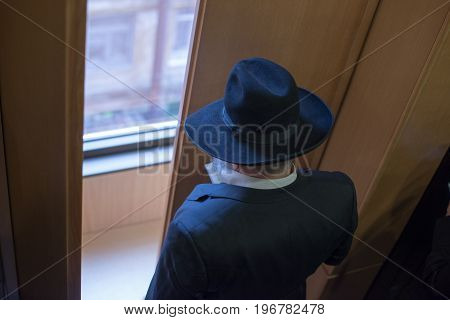 Jew Hasid Ethnic Headdress. The Jew Prays Before The Window. View From Above