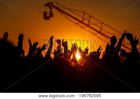 Hands up at sunset, Open air view Silhouettes of the summer festival. The light of a sun.