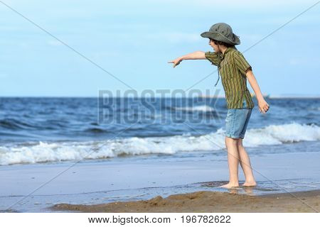 A boy stands on the sandy beach of the sea and points out into the distance with his hand.