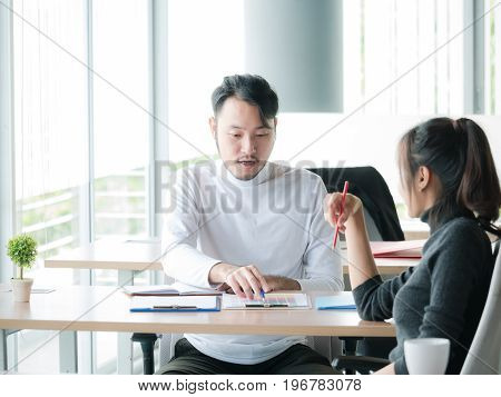 Portrait of business man and business woman working on project in modern office