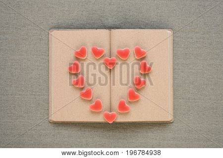 Heart made of fruit candies on an old diary with empty pages.