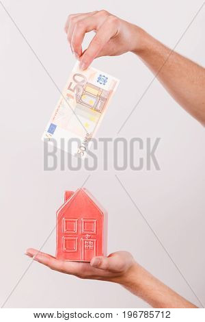 Household savings and finances economy concept. Man putting euro money into a piggy bank in the shape of a house studio shot on grey background