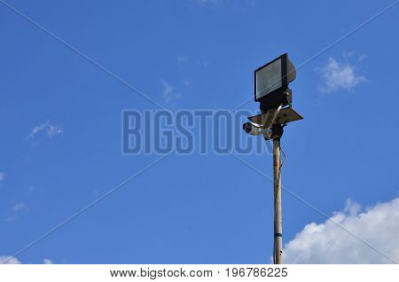 A Cctv Camera And A Square Spotlight Are Mounted On A Metal Pole Against The Blue Sky. Organized Vid
