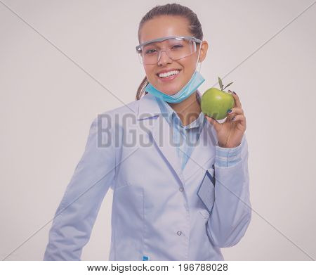 Smiling woman doctor with a green apple