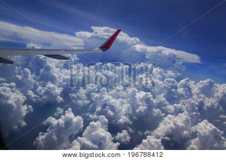 Wing of the plane flying in the sky and the sea of clouds.