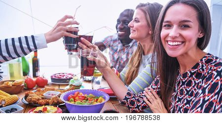 People with drinks while sitting at the dining table