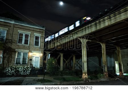 Urban elevated city of Chicago CTA subway train crossing a bridge at night next to a house and a dark alley.