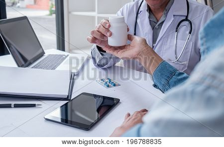 Doctor giving pills to male patient in clinic. Concept of healthcare medical treatment and insurance.